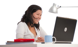 Smiling woman at her desk Stock Images