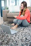 Smiling woman on her laptop and mobile phone. Smiling woman sitting on the ground on her laptop and mobile phone Royalty Free Stock Photography