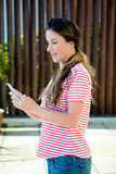 Smiling woman on her mobilephone. Smiling woman outside in the garden on her mobile phone Stock Photography