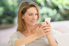 Smiling woman on her smartphone Royalty Free Stock Photography