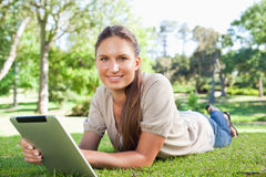 Smiling woman with her tablet computer lying on the lawn Royalty Free Stock Photos
