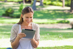 Smiling woman with her tablet computer sitting on the lawn Royalty Free Stock Photography