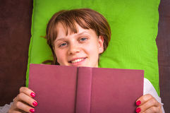 Smiling woman hides behind the book Stock Photos