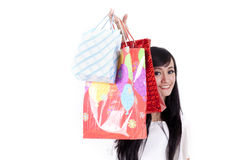 Smiling woman hiding behind her shopping bags. Beautiful Asian woman hides behind her shopping bags Stock Photography