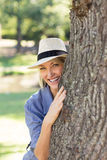 Smiling woman hiding behind tree trunk Stock Photo