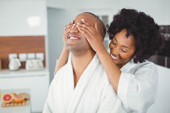 Smiling woman hiding the eyes of her husband Royalty Free Stock Photos