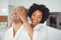 Smiling woman hiding the eyes of her husband Stock Image