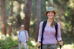 Smiling woman hiker hiking with trekking poles Royalty Free Stock Image