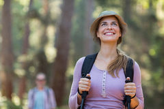 Smiling woman hiker hiking with trekking poles Stock Images