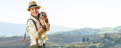 Smiling woman hiker hiking in Tuscany with retro photo camera Stock Photography