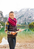 Smiling woman hiker holding map on the shores of Lake Bries Royalty Free Stock Photo