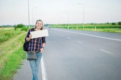 Smiling woman hitchhiker on the road is holding a blank board. Concept: to travel the world, euros, holidays, people, vacations Royalty Free Stock Photo