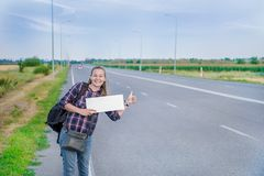 Smiling woman hitchhiker on the road is holding a blank board. Concept: to travel the world, euros, holidays, people, vacations Stock Photos