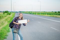 Smiling woman hitchhiker on the road is holding a blank board. Concept: to travel the world, euros, holidays, people, vacations Stock Photo