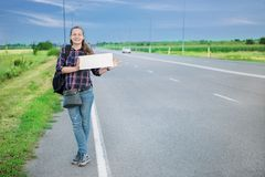 Smiling woman hitchhiker on the road is holding a blank board. Concept: to travel the world, euros, holidays, people, vacations Stock Images