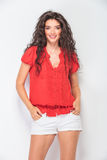 Smiling woman hoding her hands in pockets. Portrait of a young smiling woman hoding her hands in pockets Stock Photos
