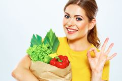 Smiling woman hold bag with green food. stock photo