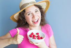 Smiling woman hold healthy and natural breakfast, oatmeal and raspberries in a bowl.  Stock Images