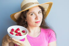 Smiling woman hold healthy and natural breakfast, oatmeal and raspberries in a bowl.  Royalty Free Stock Image