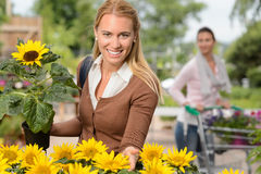 Smiling woman hold potted sunflower garden center Royalty Free Stock Photo