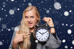 Smiling woman holding alarm clock. Christmas time concept. Smiling surprised woman holding alarm clock and pointing at it over blue background with snowflakes Stock Photography