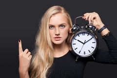 Smiling woman holding alarm clock and counting Royalty Free Stock Image