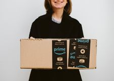 Smiling woman holding Amazon Prime parcel cardboard box stock images