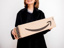 Smiling woman holding Amazon Prime parcel cardboard box royalty free stock photo