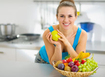 Smiling woman holding apple in kitchen Royalty Free Stock Photo
