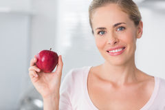 Smiling woman holding apple in right hand Royalty Free Stock Images