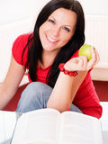 Smiling woman holding an apple and studyi Stock Images