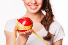 Smiling woman holding an apple and tape measure Stock Photography