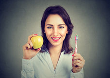 Smiling woman holding an apple and toothbrush Stock Image
