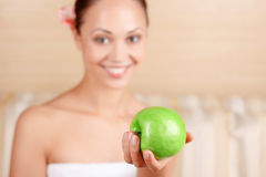 Smiling woman holding apple. It is for you. Selective focus of green apple lying in hand that beautiful lady holds while being in spa salon and expressing Stock Photo