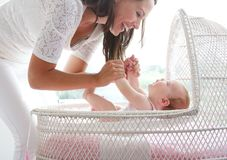 Smiling woman holding baby in cot Royalty Free Stock Photography