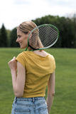Smiling woman holding badminton racquet and looking away Stock Photography