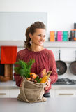 Smiling woman holding bag of autumn vegetables in kitchen Stock Photo
