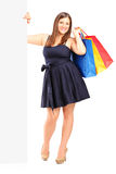 Smiling woman holding a bags behind a panel Royalty Free Stock Image