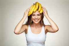 Smiling woman holding banana on head. Funny face studio  portrait Royalty Free Stock Images