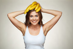 Smiling woman holding banana on head. Funny face studio  portrait Stock Photography