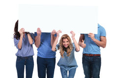 Smiling woman holding banner with her friends hiding Royalty Free Stock Image