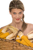 Smiling woman holding a basket filled with corn Stock Photo