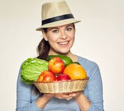 Smiling woman holding basket with fruit and vegetable. Isolated portrait Stock Photos