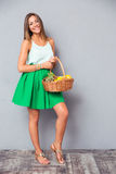 Smiling woman holding basket with fruits Royalty Free Stock Photos
