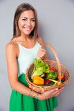 Smiling woman holding basket with vegetables Royalty Free Stock Photos