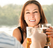 Smiling woman holding beer in outside setting Stock Photography