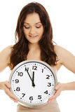 Smiling woman holding big clock. Royalty Free Stock Images