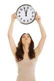 Smiling woman holding big clock. Stock Photo