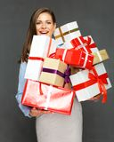 Smiling woman holding big pile of presents. Stock Photo