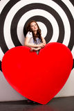 Smiling woman holding big red heart in studio Stock Images